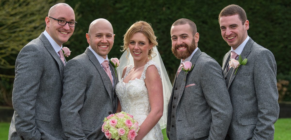 The bride stands with the groom and his ushers after their wedding at Gaynes Park