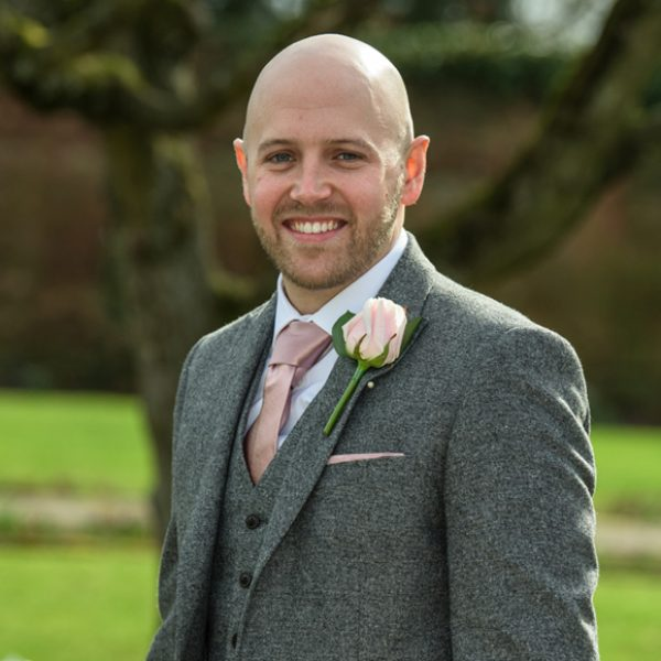 The groom wore a grey suit with blush pink tie for the natural spring wedding at Gaynes Park in Essex