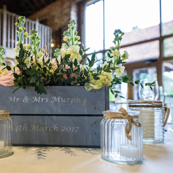 Personalised blue apple crates were filled with flowers to create natural spring wedding table centrepieces