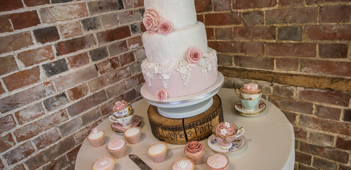 A three-tiered wedding cake was adorned with pink and white icing flowers for a spring wedding at Gaynes Park