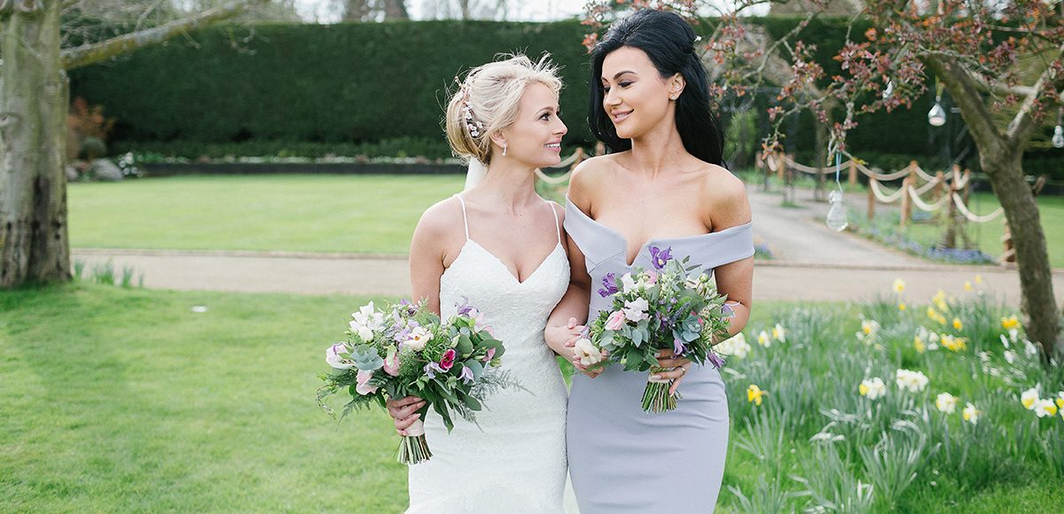 The bride and her bridesmaid enjoy a moment in the walled gardens at Gaynes Park in Essex