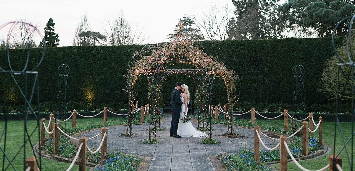 The bride and groom enjoy romantic moment away from guests under the Pavillion at Gaynes Park in Essex