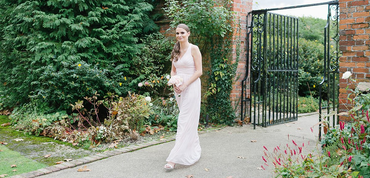 The bridesmaid wears a blush pink bridesmaid dress as she walks down the Long Walk at Gaynes Park in Essex
