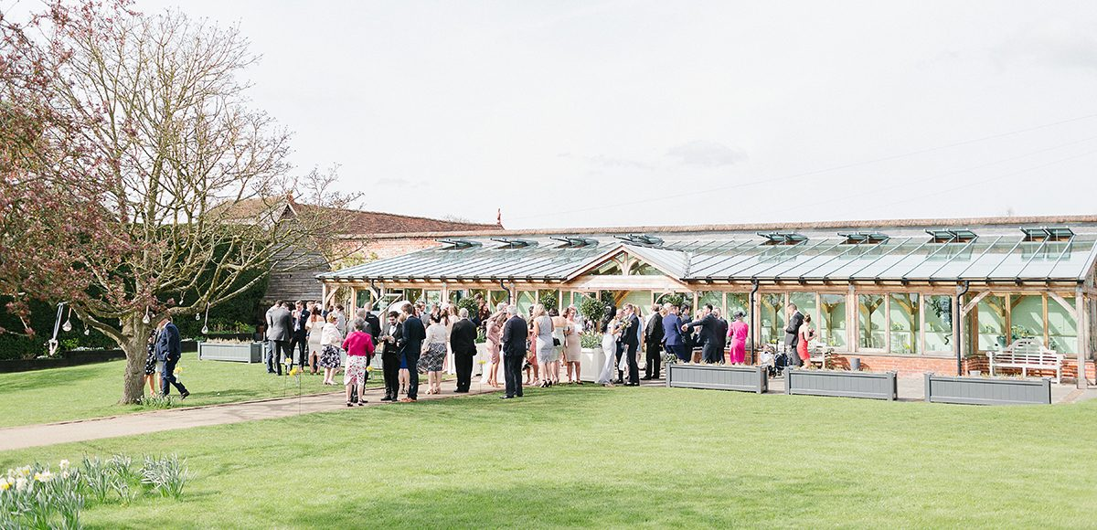 Wedding guests gathered outside the Orangery at Gaynes Park in Essex for the wedding drinks reception