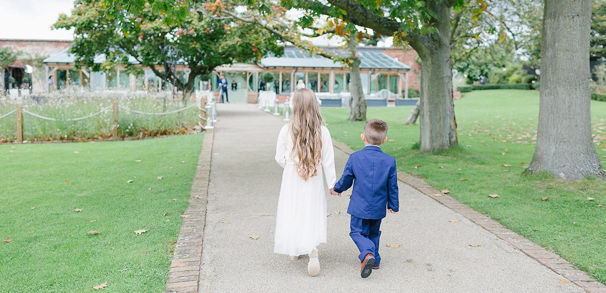 The flower girl and page boy walk hand down the Long Walk towards the wedding ceremony at Gaynes Park
