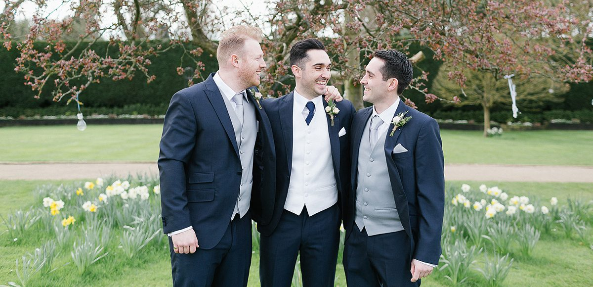 The groom and his groomsmen stand among the daffodils in the gardens at Gaynes Park in Essex