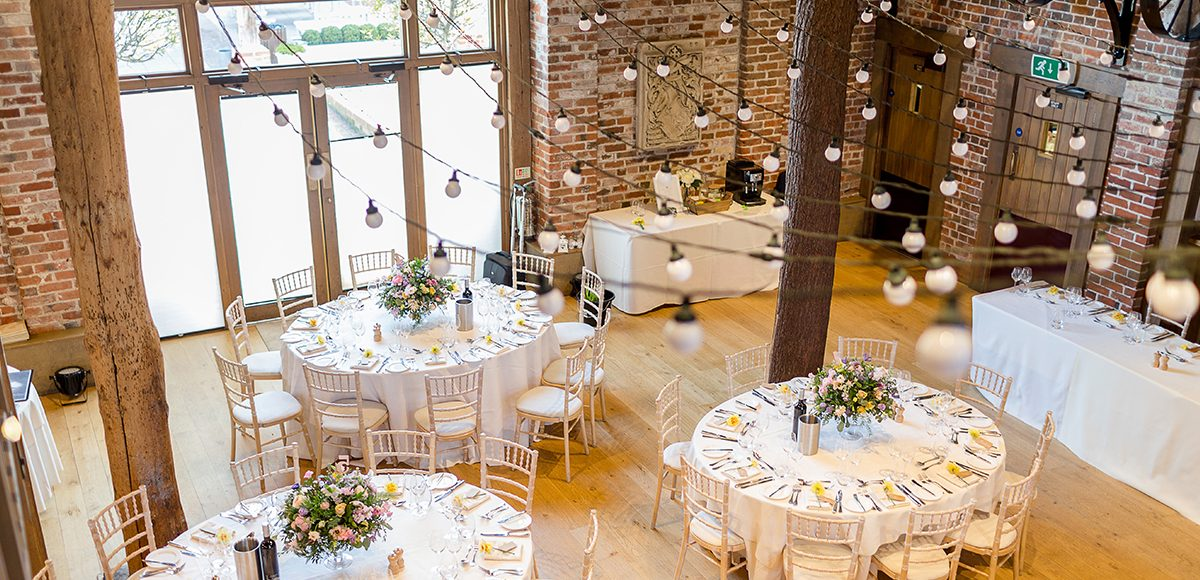 The Mill Barn at Gaynes Park is decorated with bright spring blooms for the spring wedding reception