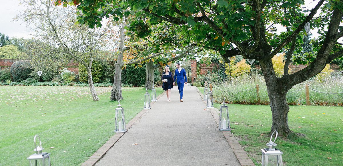 The groom and his mum walk down the Long Walk at Gaynes Park towards the wedding ceremony