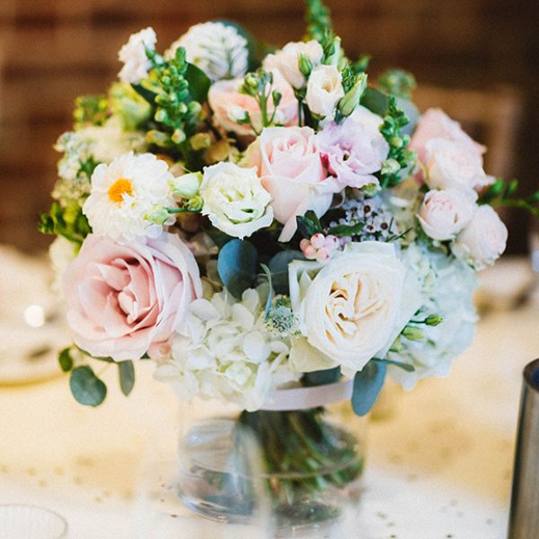 A jar of dusty pink roses adds elegance to a vintage wedding at Gaynes Park