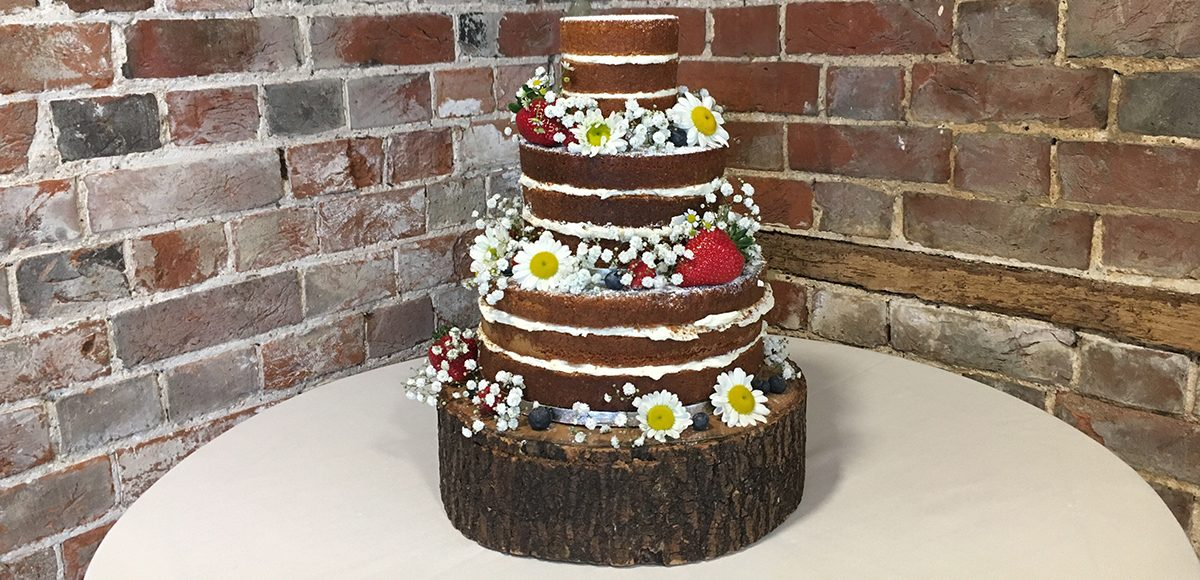 This naked wedding cake adorned with daisies and berries is perfect for a rustic wedding
