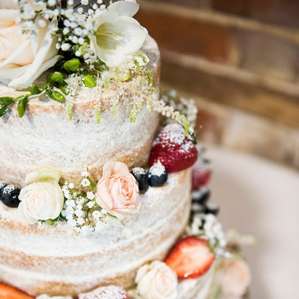 A naked wedding cake adds a rustic look to a vintage wedding at Gaynes Park