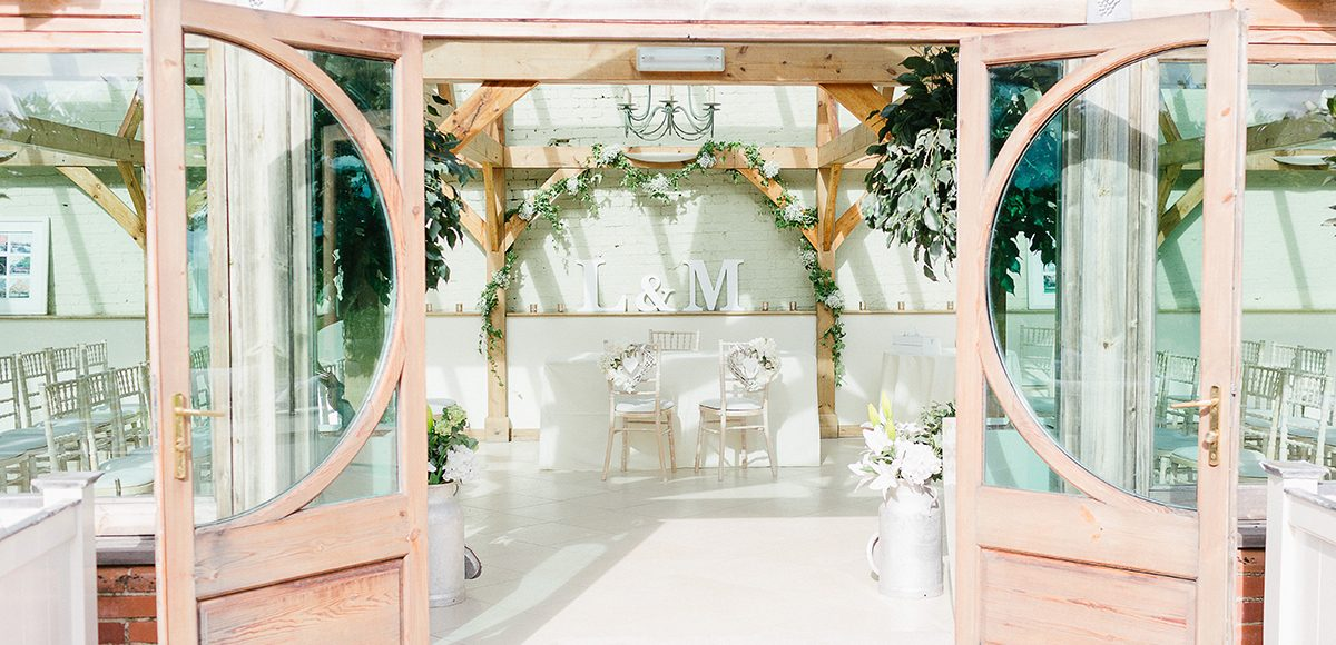 The entrance to the Orangery at the Essex wedding venue looked stunning decorated with white wedding flowers