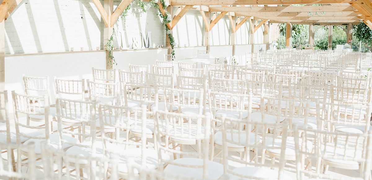 The light filled Orangery at Gaynes Park was set up with rows of Chiavari chairs for the wedding ceremony
