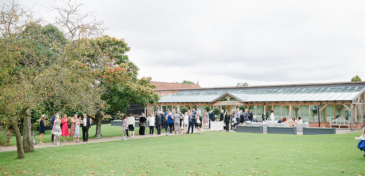 Wedding guests enjoyed wedding reception drinks outside the Orangery at Gaynes Park in Essex