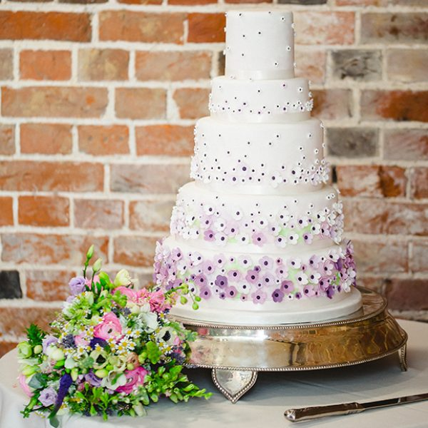 A five-tiered traditional wedding cake is decorated with small purple and white icing flowers