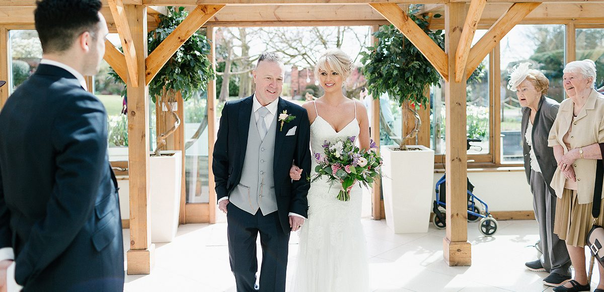 The bride was glowing as she entered the Orangery at Gaynes Park for the wedding ceremony