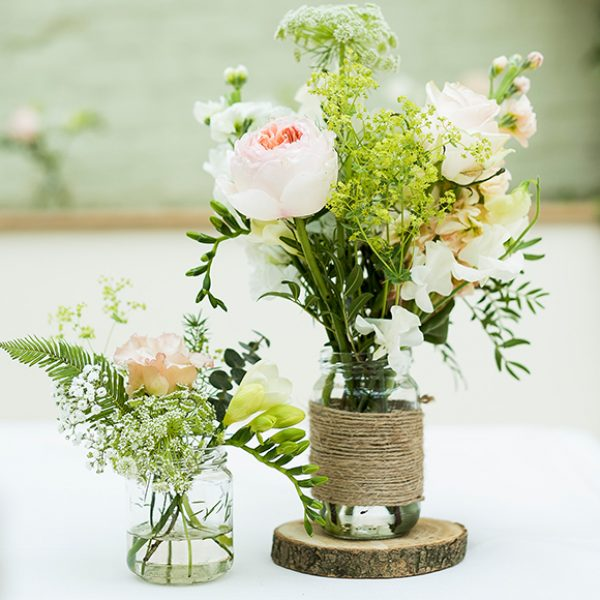 Jam jars wrapped in hessian and filled with wedding flowers create a rustic wedding look