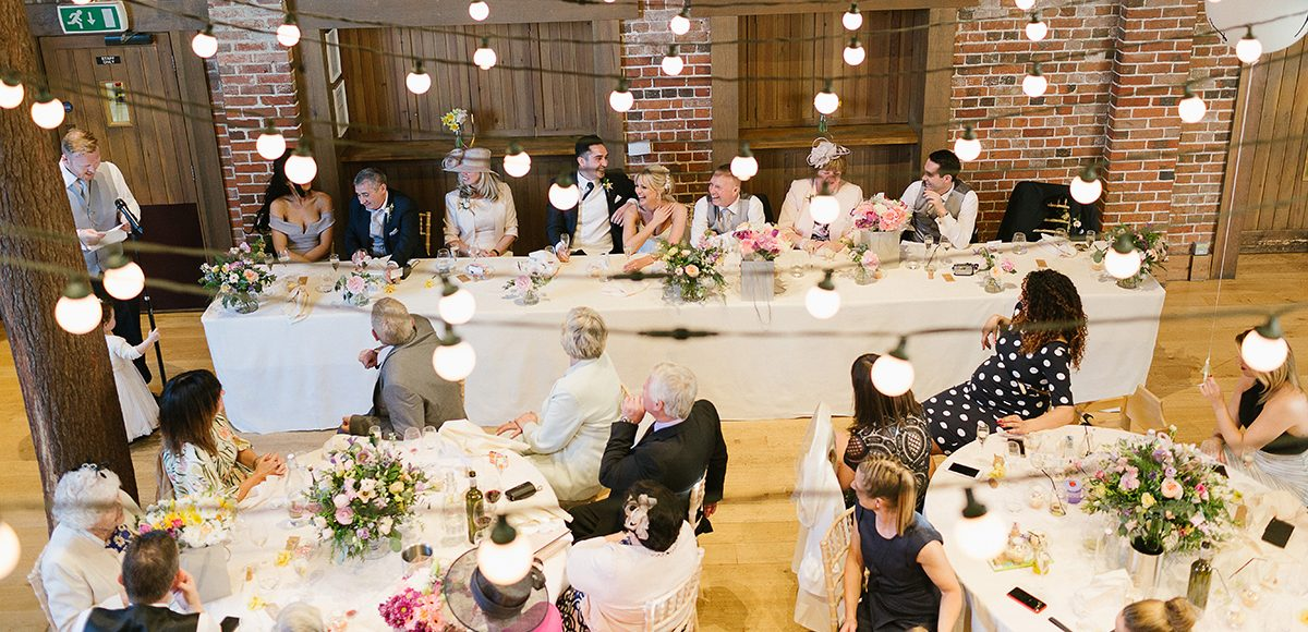 At the wedding reception in the Mill Barn at Gaynes Park in Essex guests enjoy the speech from the best man