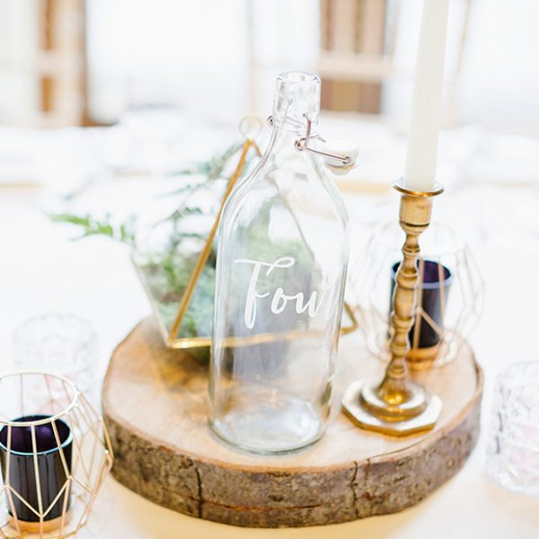 The newlyweds used glass bottles as table numbers for this rustic wedding at Gaynes Park