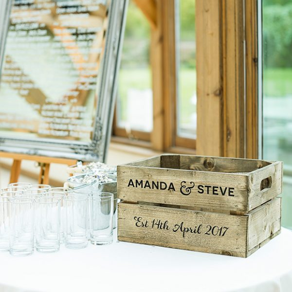 A vintage apple crate is personalized with the bride and grooms names for a wedding at Gaynes Park
