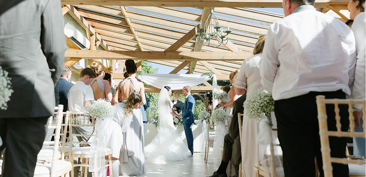 A bride and groom say their wedding vows in the Orangery at Gaynes Park