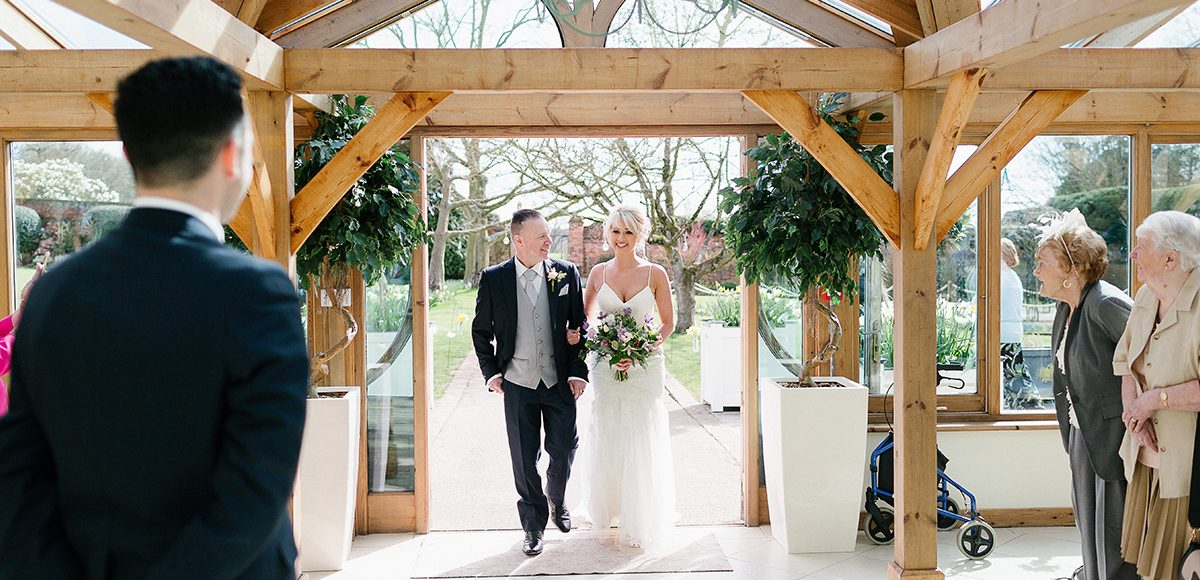 The bride and her father enter the wedding ceremony in the Orangery at Gaynes Park