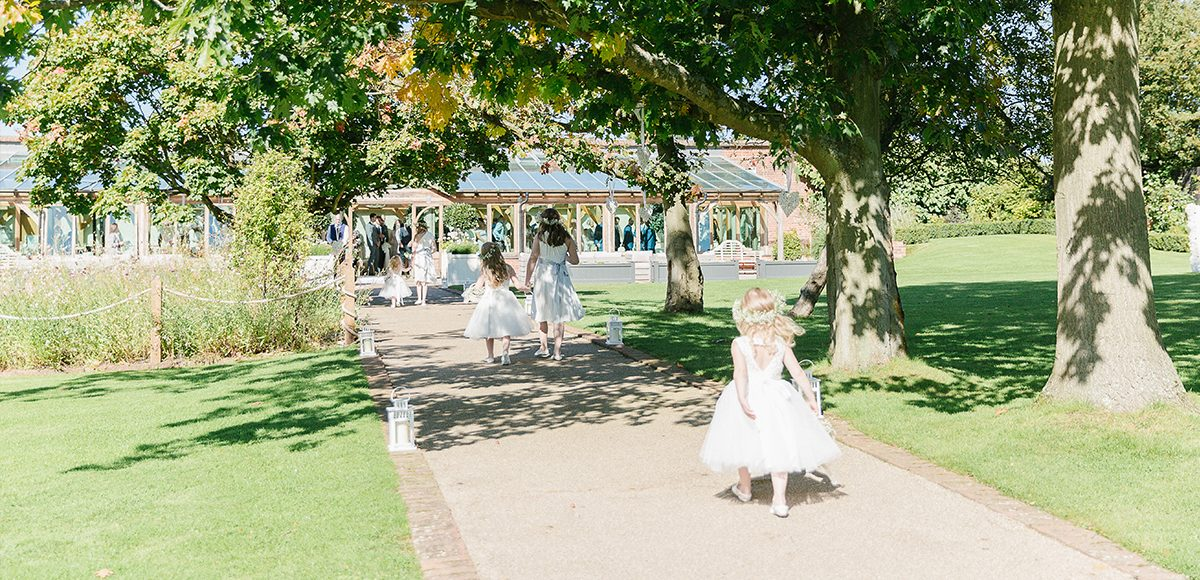 At the Essex wedding venue flower girls make their way down the garden aisle towards the wedding ceremony