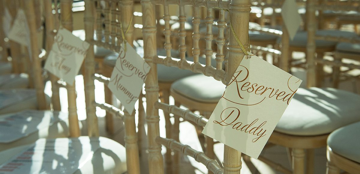 Reserved seating tags are attached to chairs in the Orangery ready for the wedding ceremony