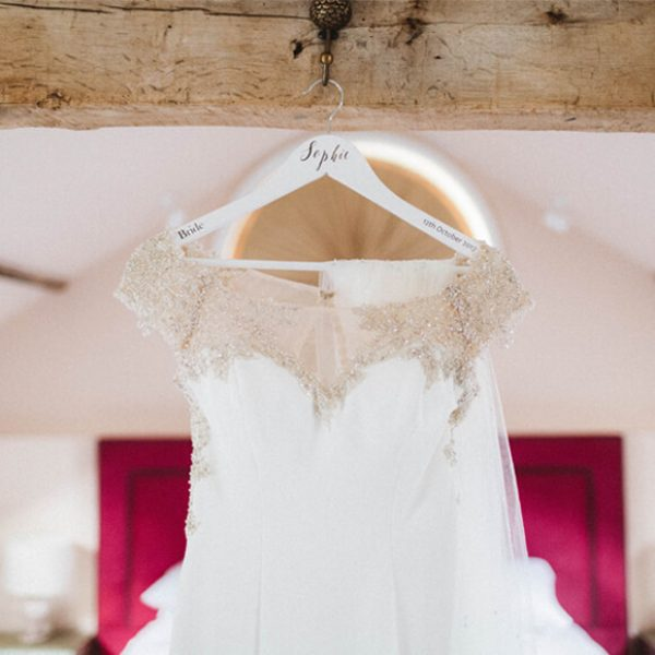 A bridal gown with delicate beaded details hangs in the Apple Loft Cottage at Gaynes Park