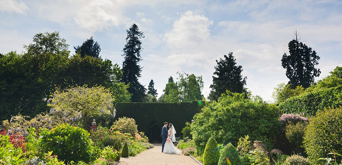 A bride and groom take a moment in the beautiful gardens at Gaynes Park on their wedding day