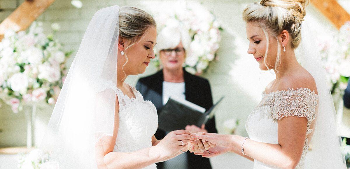 The brides exchange rings and say I do during their wedding ceremony in the Orangery at Gaynes Park
