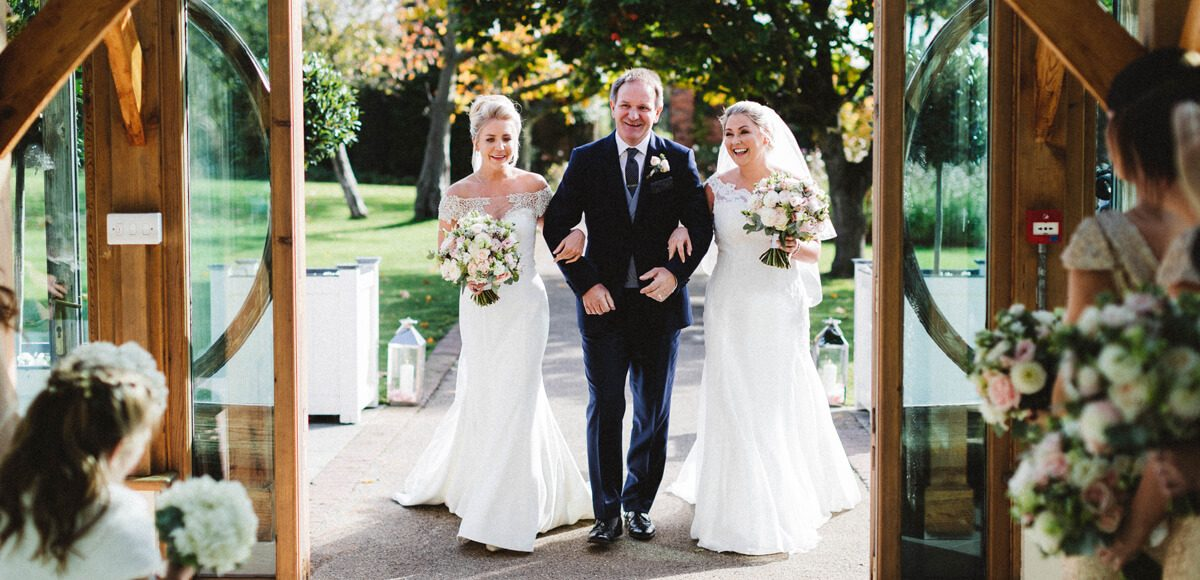 The brides walk with one of their fathers down the wedding aisle towards the Orangery at Gaynes Park