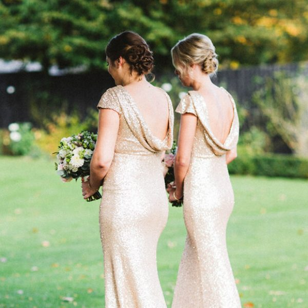 The bridesmaids wear gold dresses as they walk down the aisle towards the Orangery at Gaynes Park