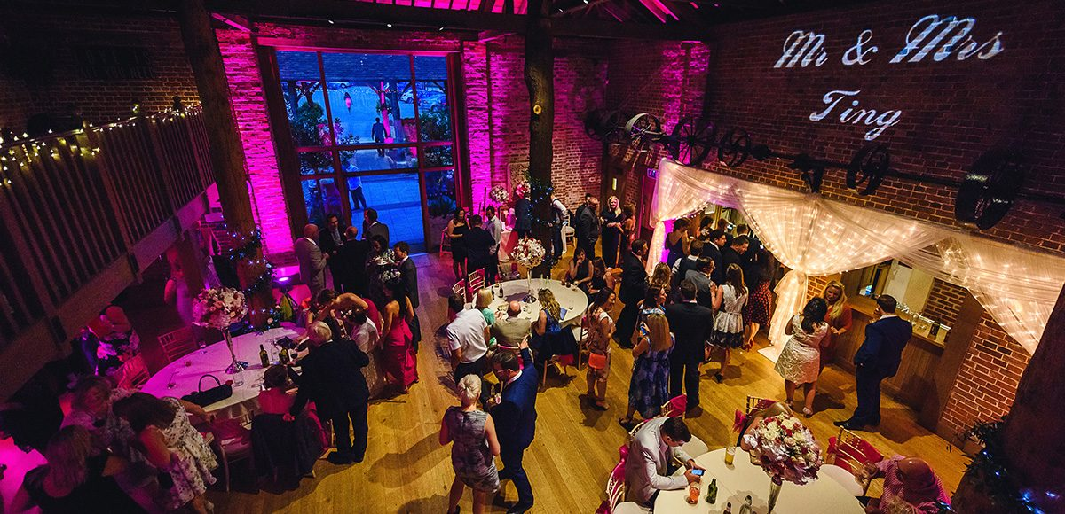 Wedding guests enjoy the evening wedding reception in the Mill Barn at Gaynes Park in Essex