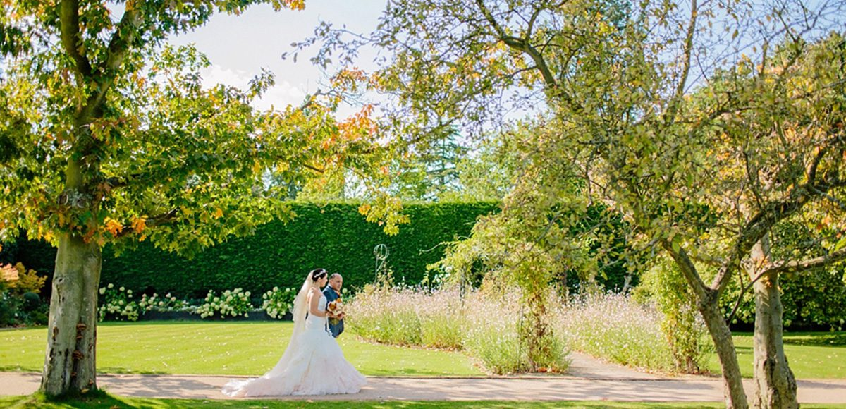 The bride and her father walk down the wedding aisle in the walled gardens at Gaynes Park in Essex