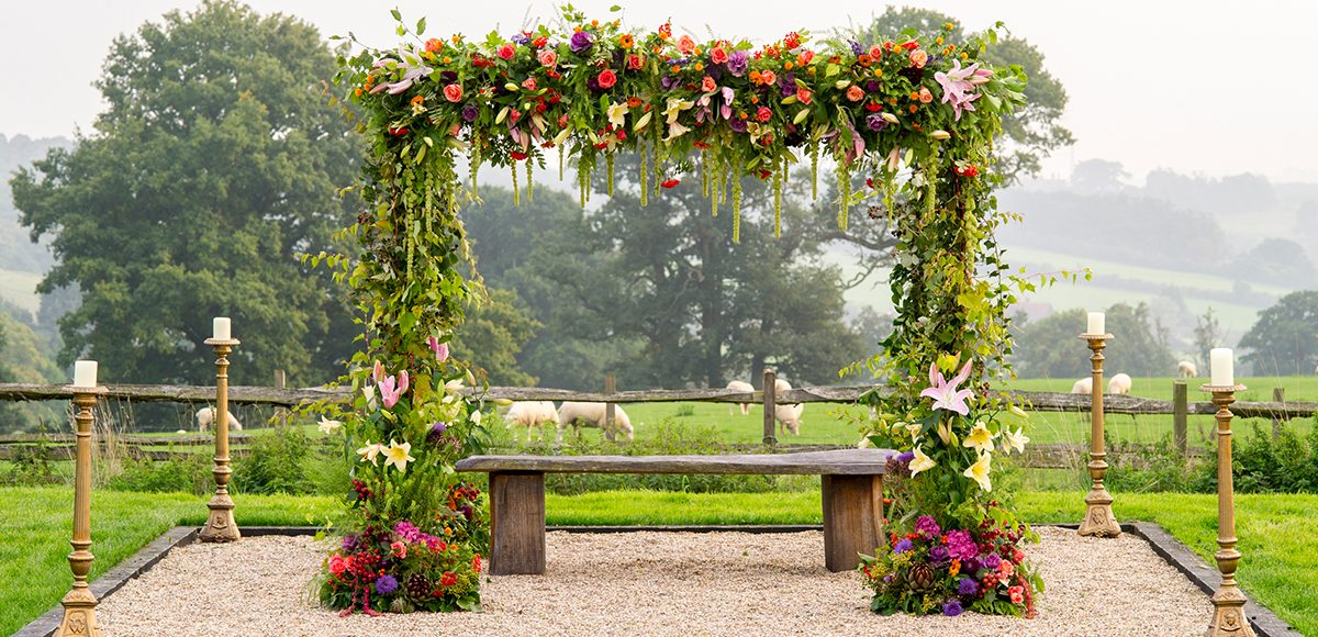 A floral wedding arch frames the stunning views that surround Gaynes Park