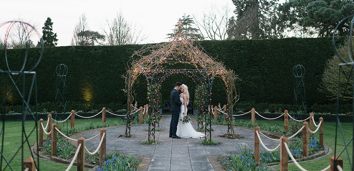Newlyweds take a moment under the Pavillion in the gardens at Gaynes Park