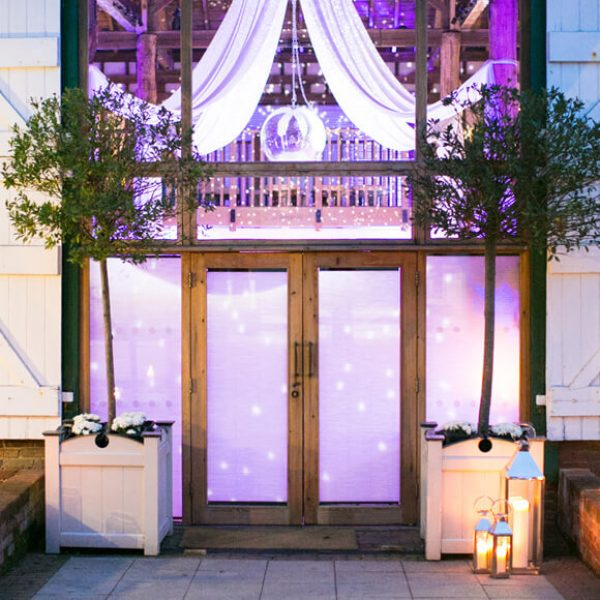 Outdoor lanterns add a warm welcome to evening guests entering the Mill Barn at Gaynes Park