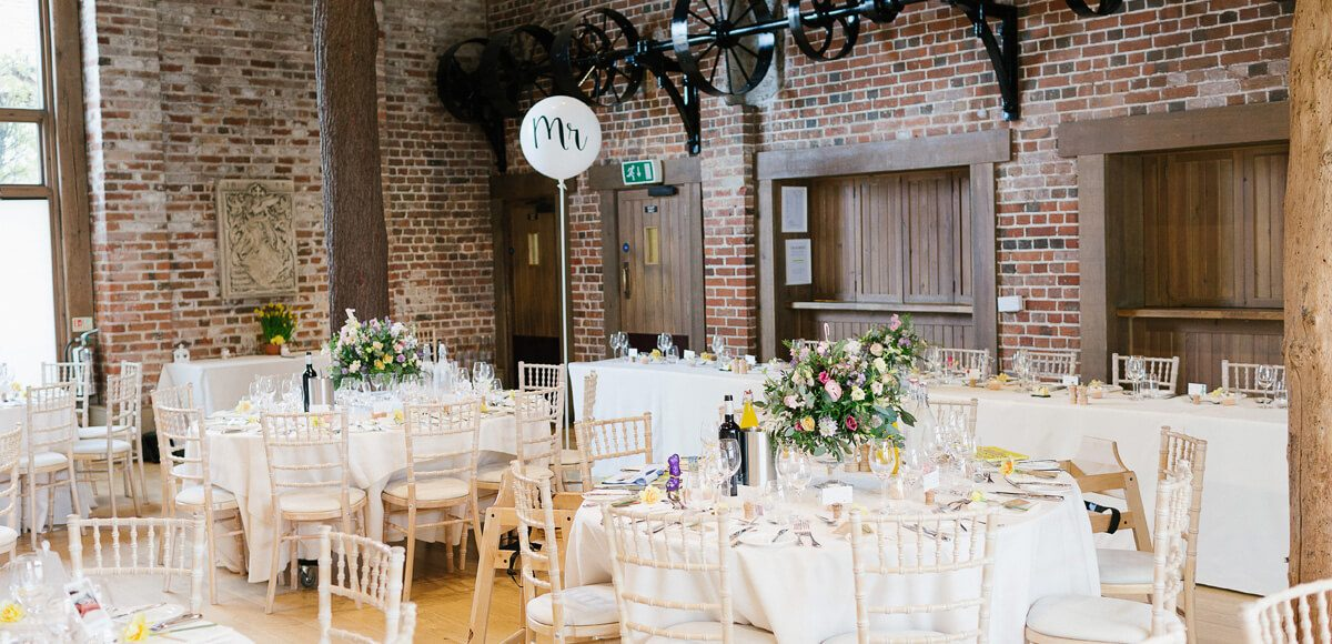 The Mill Barn at Gaynes Park is set up for a rustic wedding reception complete with bubble balloons