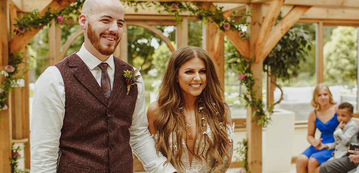 The bride and groom say their wedding vows during their ceremony at Gaynes Park in Essex