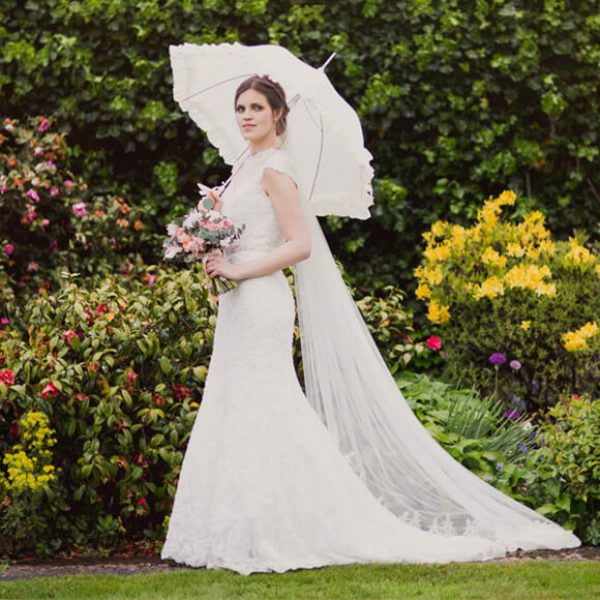 The bride looks stunning in the gardens on a rainy day at Gaynes Park wedding venue in Essex