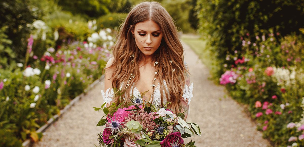 The boho bride holds a stunning wedding bouquet as she walks down the Long Walk to her wedding ceremony at Gaynes Park