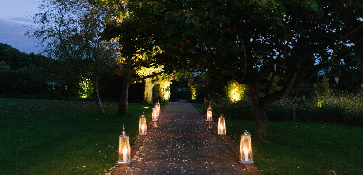 Lanterns light up the wedding aisle in the Walled Gardens during an evening reception at Gaynes Park in Essex