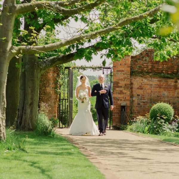 The bride to be walks down the wedding aisle in the Walled Garden at Gaynes Park on her summer wedding day