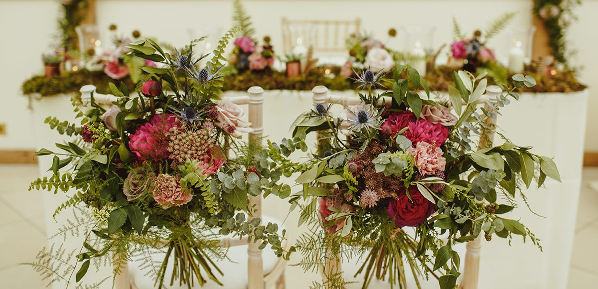 Rustic wedding flowers adored the chairs and table in the Orangery at Gaynes Park for a summer wedding ceremony