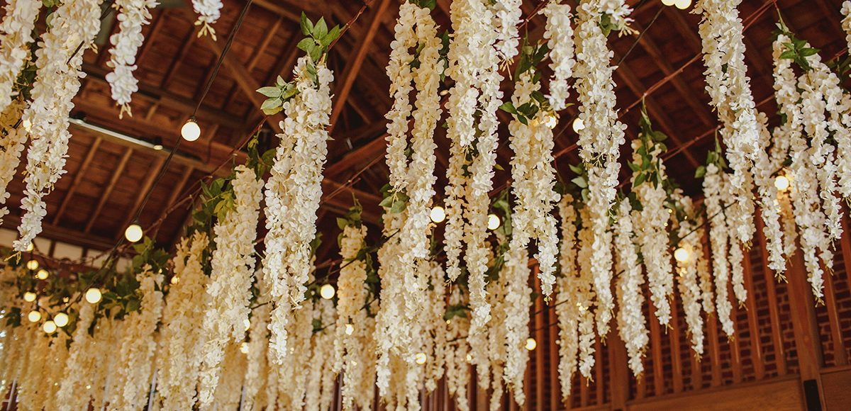 The bride hung wisteria in the Mill Barn at Gaynes Park for a magical touch to her woodland themed summer wedding