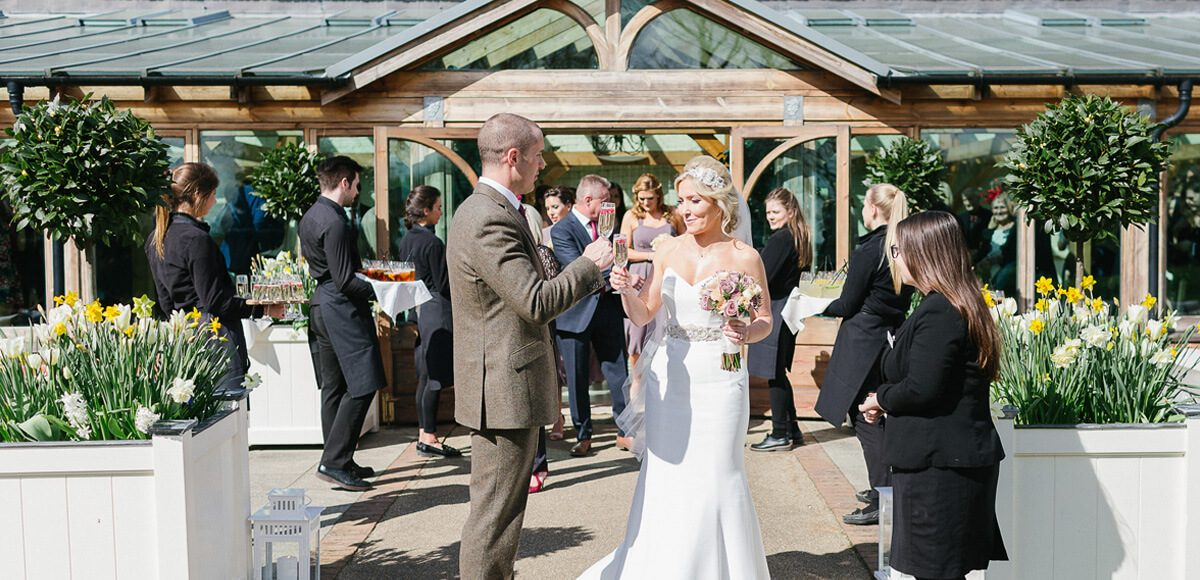 Newlyweds enjoy their wedding drinks reception in the beautiful Walled Gardens at Gaynes Park in Essex