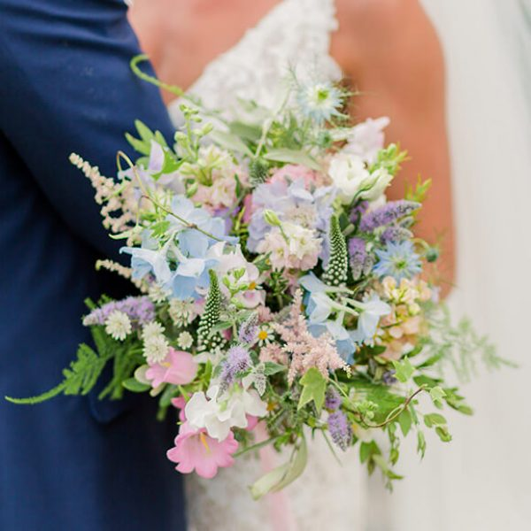 A beautiful spring wedding bouquet adds a pop of colour to a wedding at Gaynes Park wedding venue in Essex