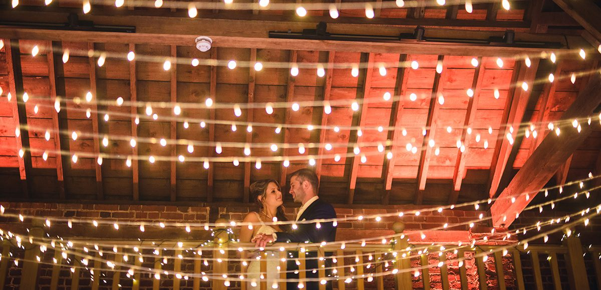 Fairylights are added to the Mill Barn at Gaynes Park for added sparkle at a rustic wedding