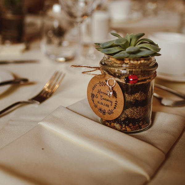 A couple gave guests succulents in jam jars as a rustic wedding favour for their Gaynes Park wedding